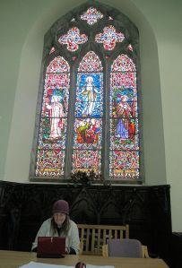The stained-glass window and Shari at the table. Photo by Bill Burke.